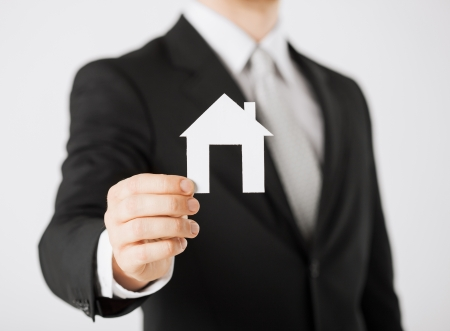 accommodation broker: picture of man hand holding paper house