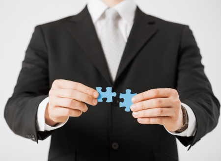 linking: close up of man trying to connect puzzle pieces  Stock Photo