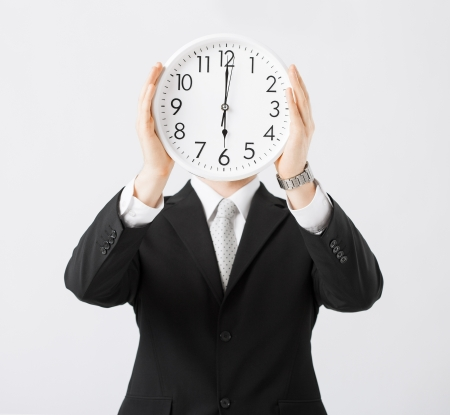 man covering his face with wall clock Stock Photo