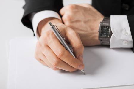 persona escribiendo: imagen de hombre de negocios escrito algo sobre el papel