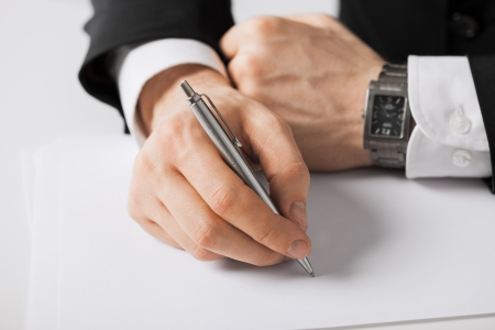 taking: picture of businessman writing something on the paper