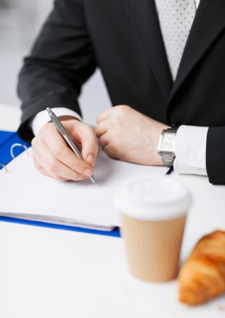 coffee time: businessman on his coffee break making notes