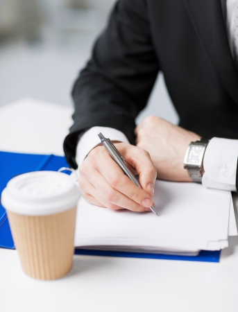 take a note: businessman with coffee cup writing something on the paper