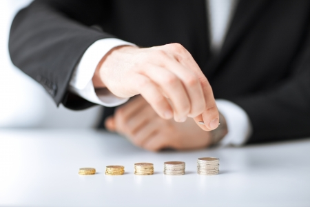 Bild der Mann, der Stapel von Münzen in einer Zeile Standard-Bild - 20074879
