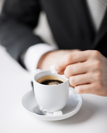 close up of man putting sugar into coffee photo