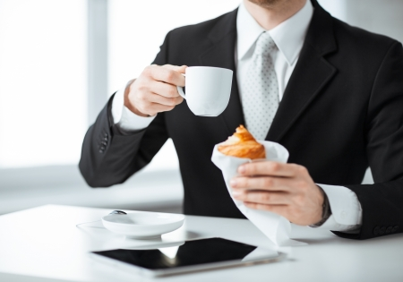 office wear: businessman with tablet pc, cup of coffee and croissant
