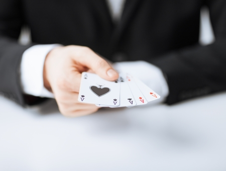 close up of man hand showing four aces