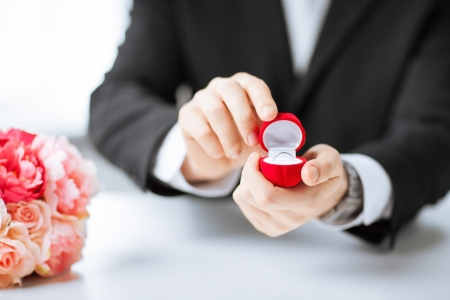 picture of man with gift box and wedding ring photo