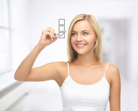 checkbox: smiling woman in white shirt drawing red checkmark into checkbox Stock Photo