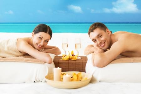 massage homme: photo du couple sur la plage boire du champagne