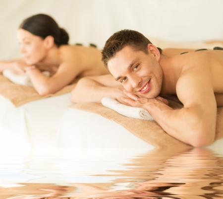 mimos: Foto de joven en el salón de spa con piedras calientes