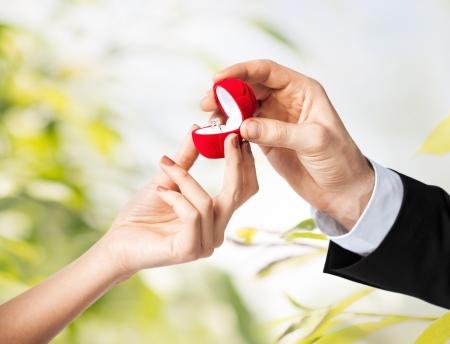 paar handen met trouwring en geschenkdoos