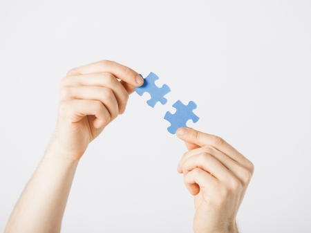 matching: close up of two hands trying to connect puzzle pieces Stock Photo