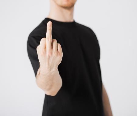 真ん中の指を示す人間のクローズ アップ 写真素材