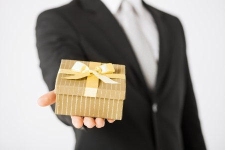 giving: close up of man hands holding gift box. Stock Photo