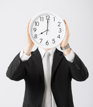 wasting: man covering his face with wall clock Stock Photo