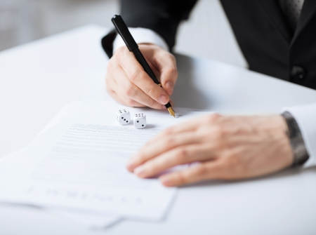 risk management: picture of man hands with gambling dices signing contract