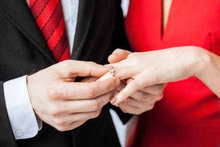 anillo de compromiso: foto del hombre que pone el anillo de bodas en la mano de mujer