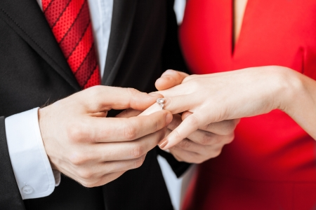 putting up: picture of man putting  wedding ring on woman hand Stock Photo