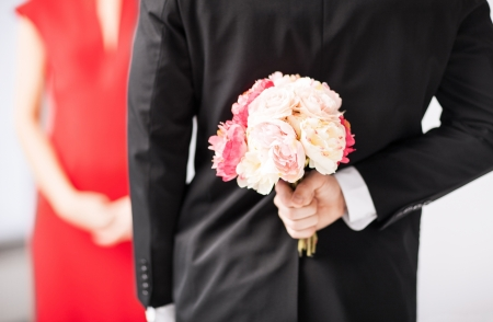 man hiding bouquet of flowers behind his back  photo