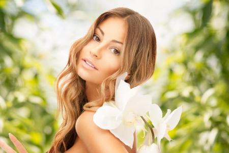 foto van mooie vrouw met orchidee bloem Stockfoto