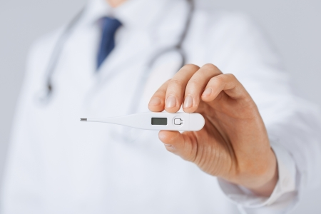 digital thermometer: bright close up of male doctor with thermometer