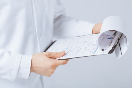 close up of male doctor holding prescription paper in hand photo