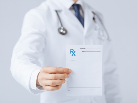 family physician: close up of male doctor holding rx paper in hand Stock Photo