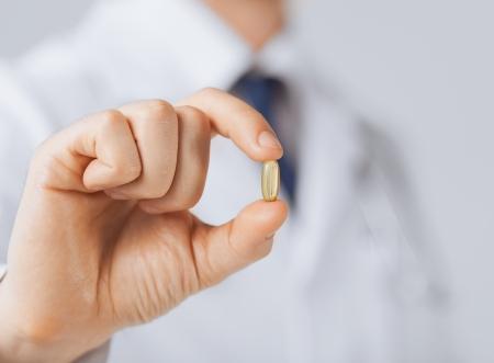 약물 치료: 하나의 캡슐을 보여주는 의사의 손 사진