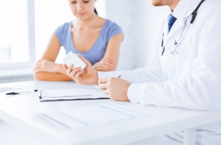 patient and doctor: close up of patient and doctor prescribing medication