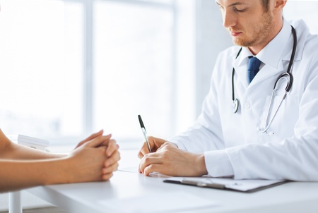 doctor's appointment: close up of patient and doctor taking notes Stock Photo