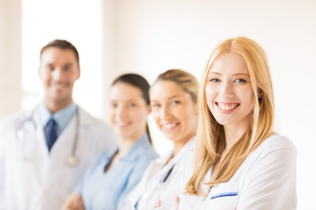 family doctor: attractive female doctor in front of medical group Stock Photo