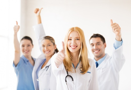 attractive female doctor with group of doctors showing thumbs up photo