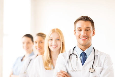 clinical staff: attractive male doctor in front of medical group Stock Photo