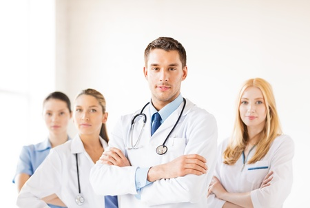 attractive male doctor in front of medical group Stock Photo