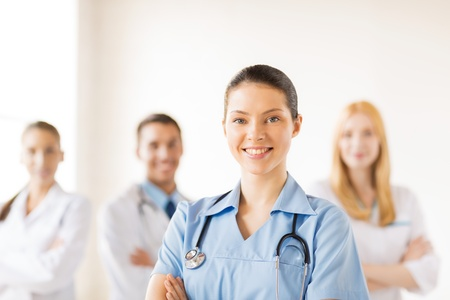 attractive female doctor or nurse in front of medical group Imagens