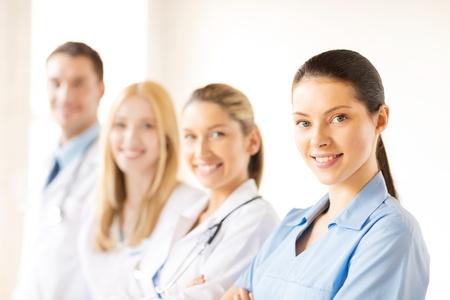 grupo de médicos: atractiva mujer médico o enfermera frente a grupo médico
