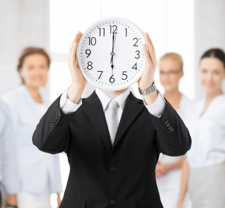 rushing hour: man covering his face with wall clock Stock Photo