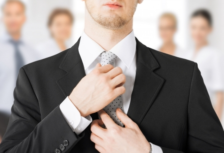 close up of man adjusting his tie photo