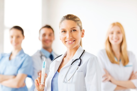 anesthesia: group of medics with female doctor holding syringe with injection Stock Photo