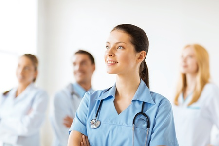 physiotherapists: attractive female doctor or nurse in front of medical group Stock Photo