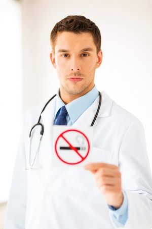 anti tobacco: male doctor holding no smoking sign in hands