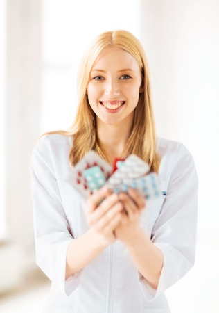 picture of young female doctor with pack of pills