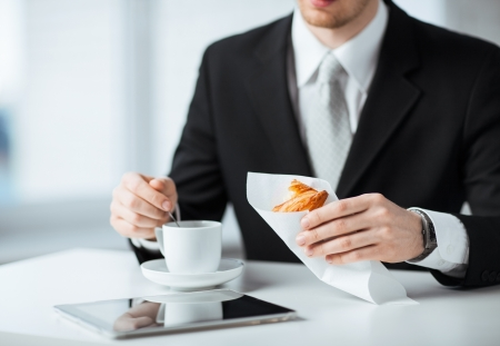 man with tablet pc, cup of coffee and croissant photo