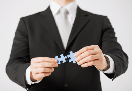 business symbols metaphors: close up of man trying to connect puzzle pieces  Stock Photo