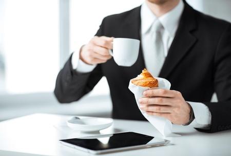 Gesch?ftsmann mit Tablette-PC, Tasse Kaffee und Croissant Lizenzfreie Bilder
