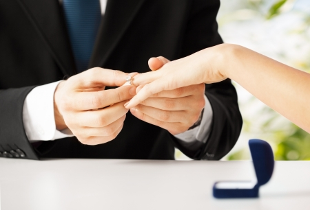약혼: 남자는 여자 손에 결혼 반지를 넣는 사진 스톡 사진