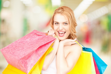 attractive woman holding color shopping bags in mall photo