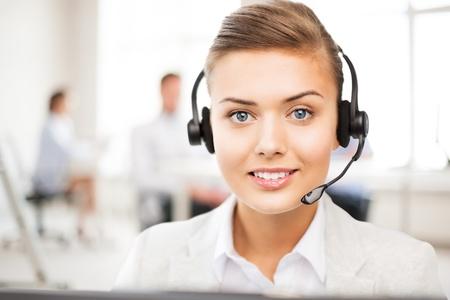 helpline: friendly female helpline operator with headphones in call centre Stock Photo
