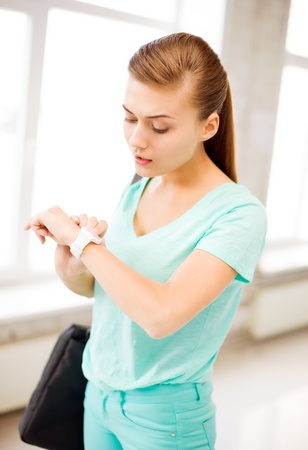 girl with a wristwatch: picture of surprised student girl looking at wristwatch